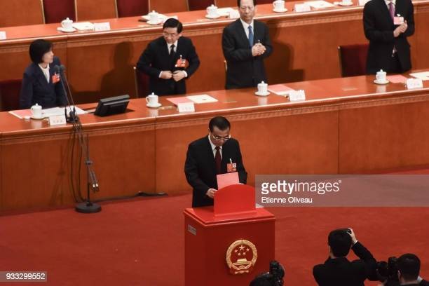 Chinese Premier Li Keqiang votes during the sixth plenary session of the National People's Congress at the Great Hall of the People on March 18 2018...