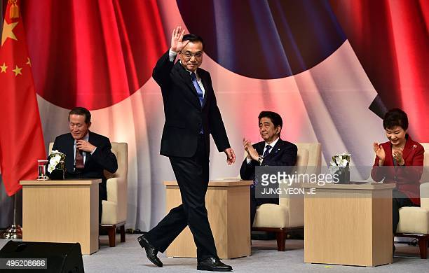 Chinese Premier Li Keqiang waves after his speech as South Korean President Park GeunHye and Japanese Prime Minister Shinzo Abe applaud during a...