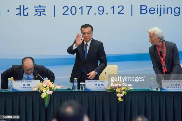 Chinese Premier Li Keqiang waves as he leaves the conference while standing between President Jim Yong Kim of the World Bank and Managing Director...
