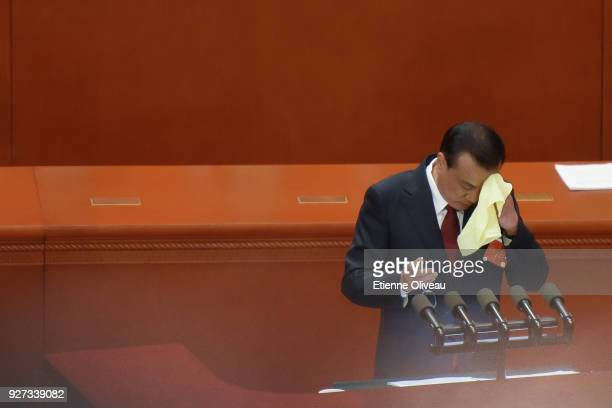 Chinese Premier Li Keqiang wipes his forehead during his speech for the opening of the 13th National People's Congress at The Great Hall of People on...