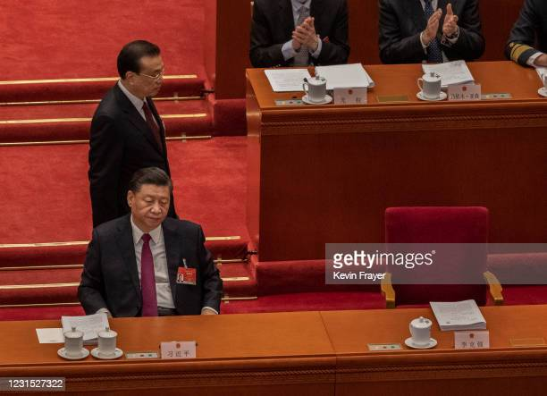 Chinese Premier Li Keqiang,top, walks by President Xi Jinping following his speech at the opening session of the National People's Congress at the...