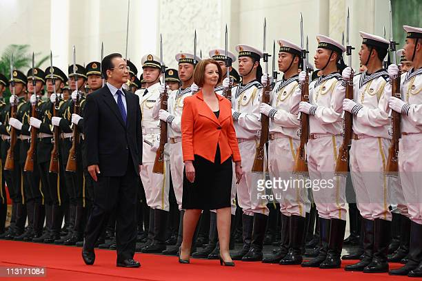 Chinese Premier Wen Jiabao accompanies Australian Prime Minister Julia Gillard to view an honour guard during a welcoming ceremony inside the Great...