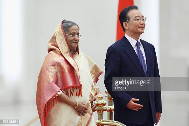 Chinese Premier Wen Jiabao and Premier of the People's Republic of Bangladesh Ms Sheikh Hasina listen to their national anthems during a welcoming...