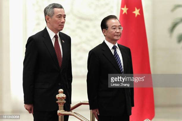 Chinese Premier Wen Jiabao and Singapore Prime Minister Lee Hsien Loong listen to their national anthems during a welcoming ceremony at the Great...