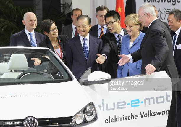 Chinese Premier Wen Jiabao gets a little encouragement to climb into a Volswagen EOS electric car by German Chancellor Angela Merkel and Volkswagen...