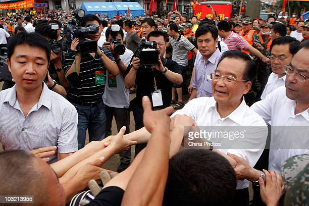 Chinese Premier Wen Jiabao greets local residents during his visit to floodhit Yongji County on August 3 2010 in Kouqian Jilin Province China...
