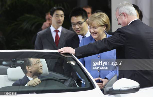 Chinese Premier Wen Jiabao sits behind the steering wheel of a Volkswagen EOS electric car as German Chancellor Angela Merkel and Volkswagen CEO...