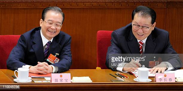 Chinese Premier Wen Jiabao talks to propaganda chef Li Changchun during the closing session of the annual National People's Congress at the Great...