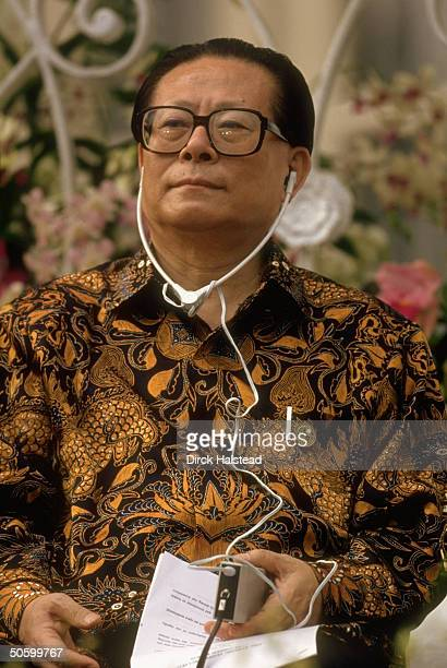 Chinese Pres Jiang Zemin sporting batik shirt wearing earphones during AsiaPacific Economic Cooperation summit
