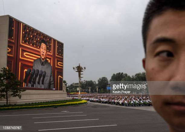 Chinese President and Chairman of the Communist Party Xi Jinping is seen on a screen as the crowd listens during his speech at a ceremony marking the...