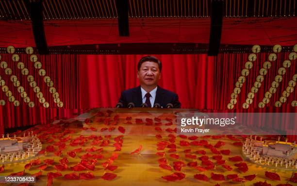 Chinese President and Chairman of the Communist Party Xi Jinping appears on a large screen as performers dance during a mass gala marking the 100th...