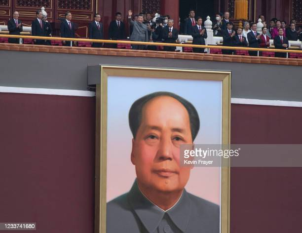 Chinese President and Chairman of the Communist Party Xi Jinping, top center, waves to the crowd after his speech above the portrait of the late...
