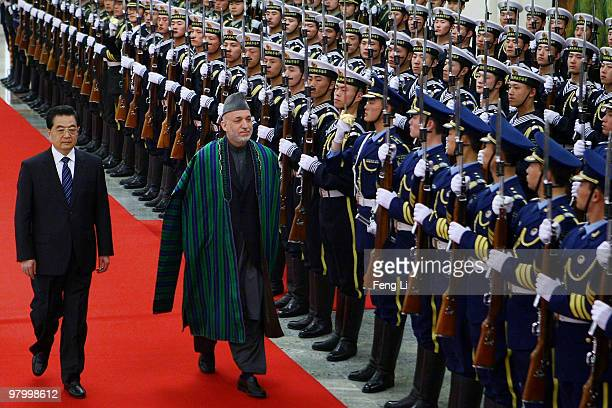 Chinese President Hu Jintao accompanies Afghan President Hamid Karzai to view an honour guard during a welcoming ceremony inside the Great Hall of...