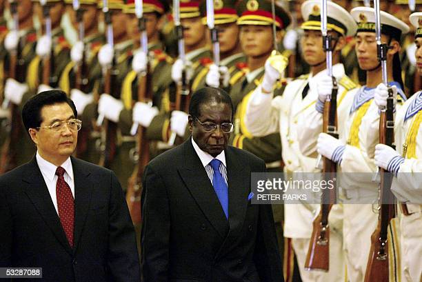 Chinese President Hu Jintao accompanies Zimbabwe President Robert Mugabe at a welcome ceremony in the Great Hall of the People in Beijing 26 July...