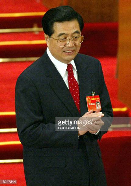 Chinese President Hu Jintao acknowledges the applause from delegates as he arrives for the second day of the 10th National People's Congress at the...