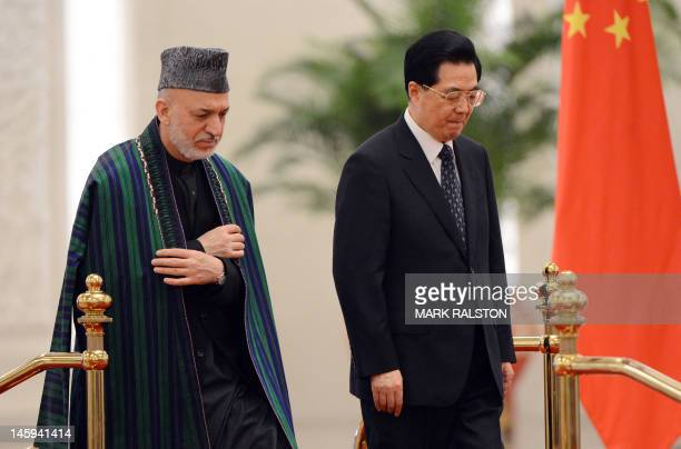 Chinese President Hu Jintao and Afghan President Hamid Karzai prepare to review an honour guard during his welcoming ceremony at the Great Hall of...