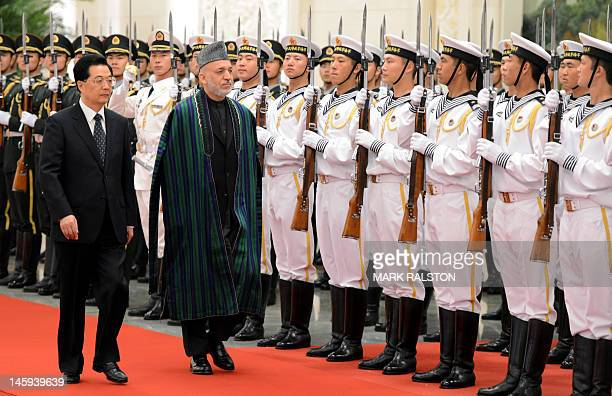 Chinese President Hu Jintao and Afghan President Hamid Karzai review an honour guard during his welcoming ceremony at the Great Hall of the People in...
