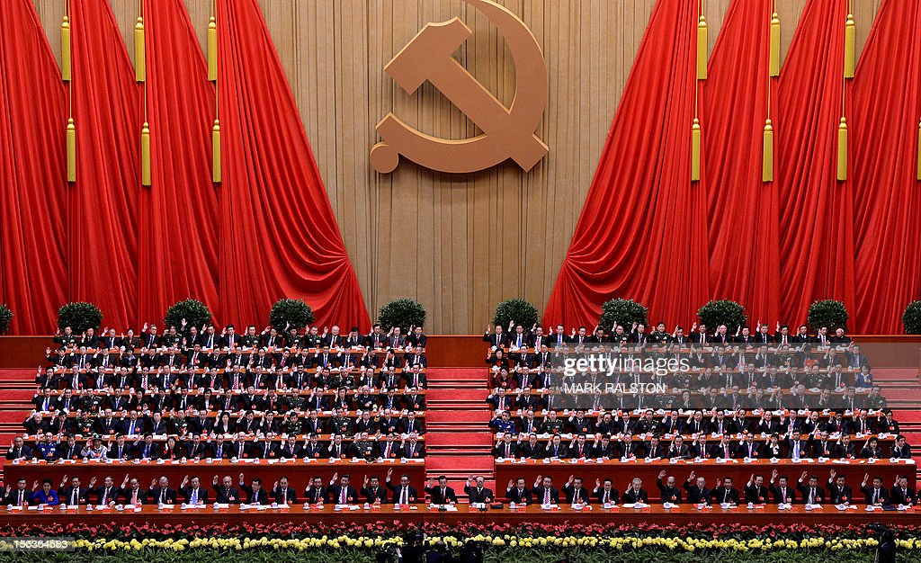 Chinese President Hu Jintao (Centre L) and former President Jiang Zemin (Centre R) with members of the Presidium raise the hands during the closing ceremony of the Party Congress at the Great Hall of the People in Beijing on November 14, 2012. China's Communist Party will on November 15 unveil the new set of top leaders who will run the country for the next decade, one day after its week-long congress ends. AFP PHOTO/Mark RALSTON