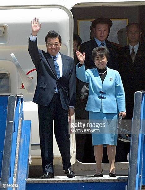 Chinese President Hu Jintao and his wife wave upon their arrival in Santiago, 18 November 2004, to attend the APEC Summit to be held in this city....