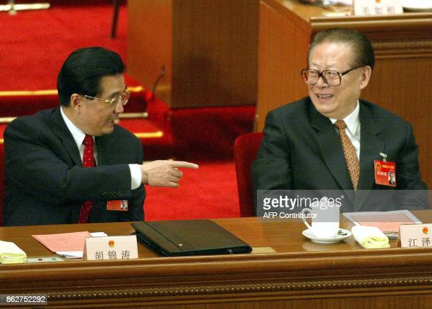 Chinese President Hu Jintao gestures toward former president Jiang Zemin during the closing session of the National People's Congress in the Great...