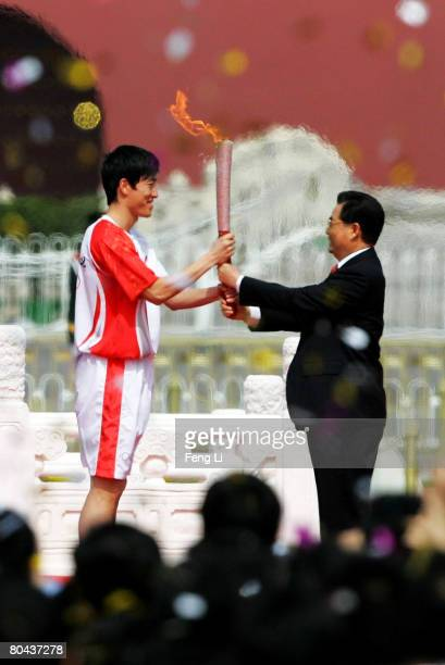 Chinese President Hu Jintao hands the Olympic torch to Olympic hurdler and gold medallist Liu Xiang during the welcome ceremony for the Olympic flame...
