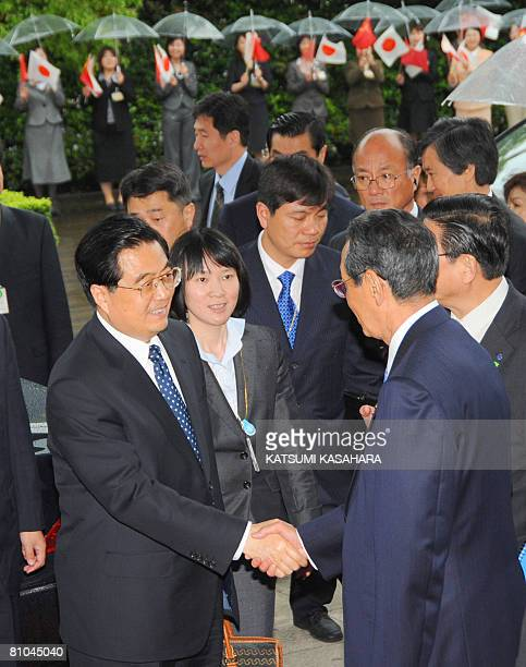 Chinese President Hu Jintao is welcomed by Kunio Nakamura, chairman of Panasonic, at his arrival at the Panasonic head office in Kadoma city in Osaka...