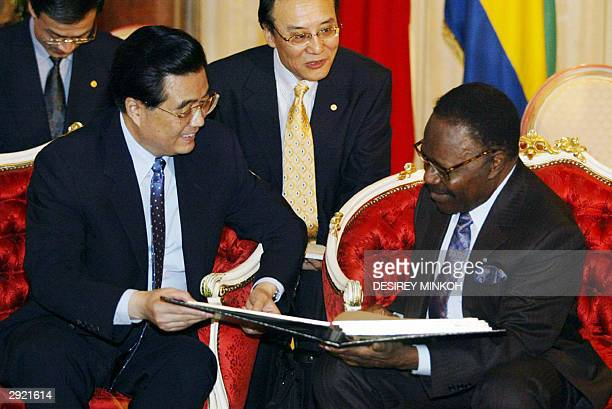 Chinese President Hu Jintao looks at Gabon's president Omar Bongo photo album showing his trip in China, at the presidential palace in Libreville, 02...