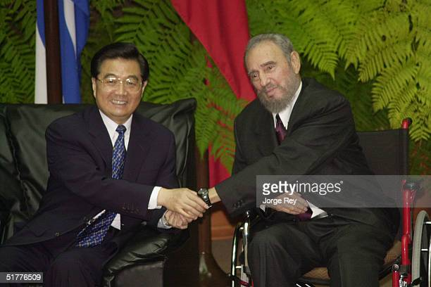 Chinese President Hu Jintao shakes hands with Cuban President Fidel Castro who is recovering from injuries suffered in a fall during a meeting at the...