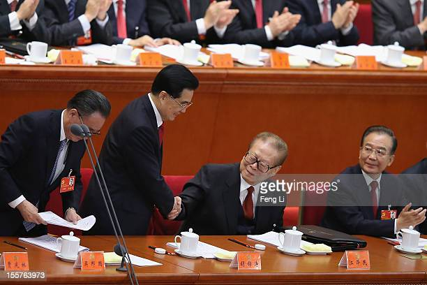 Chinese President Hu Jintao shakes hands with former Chinese President Jiang Zemin after the speech of the opening session of the 18th Communist...