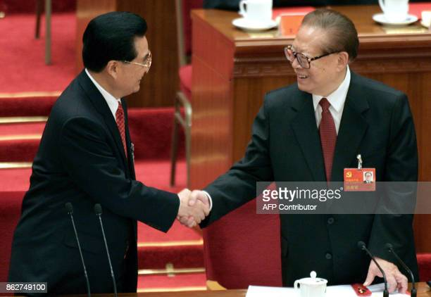 Chinese President Hu Jintao shakes hands with former president Jiang Zemin after the closing session of the 17th Communist Party Congress at the...