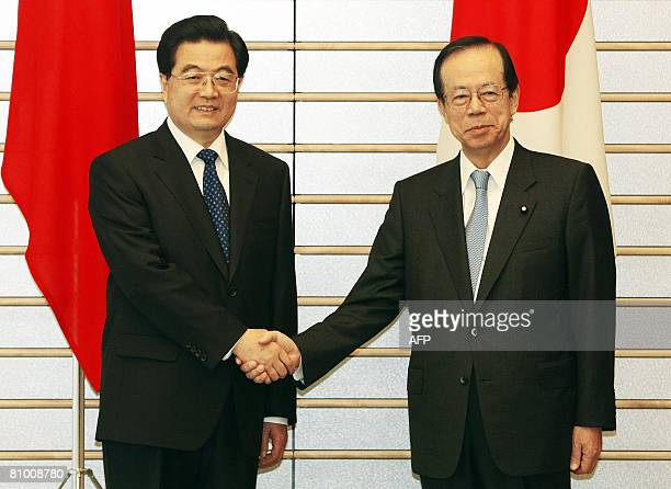 Chinese President Hu Jintao shakes hands with Japanese Prime Minister Yasuo Fukuda at the start of their meeting at the latter's official residence...