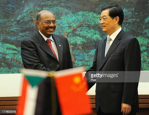 Chinese President Hu Jintao shakes hands with Sudan's leader Omar alBashir during the signing ceremony at the Great Hall of the People on June 29...