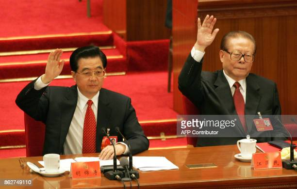 Chinese President Hu Jintao together with former president Jiang Zemin raise their hand to vote during the closing session of the 17th Communist...