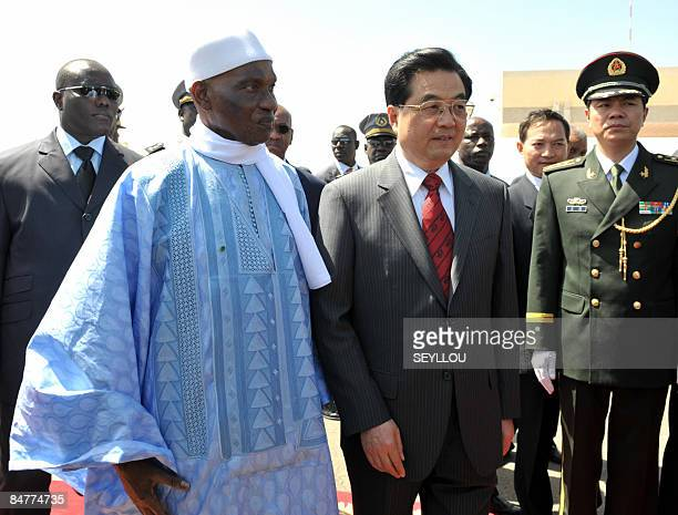 Chinese president Hu Jintao walks with Senegal president Abdoulaye Wade as he arrives at the airport on February 13, 2009 for a two day visit to...
