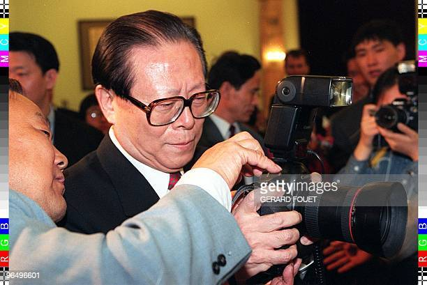 Chinese President Jiang Zemin gets an instruction on how to use a camera from a Chinese news photographer as he waits for French President Jacques...