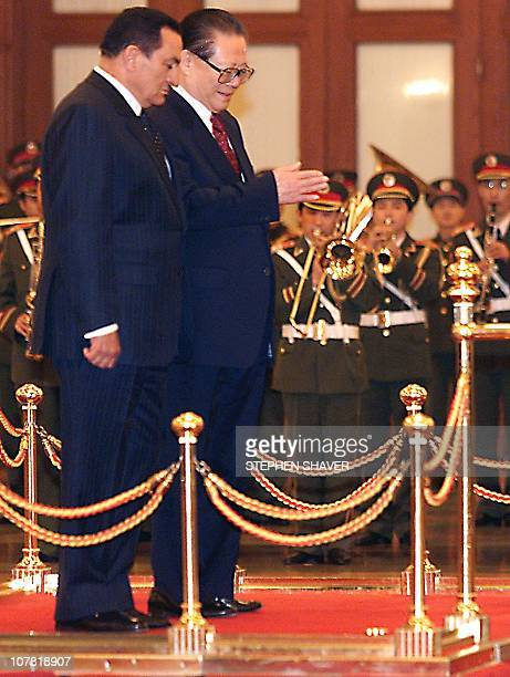 Chinese President Jiang Zemin invites Eygptian President Hosni Mubarak off the podium to inspect a military honour guard during a welcoming ceremony...