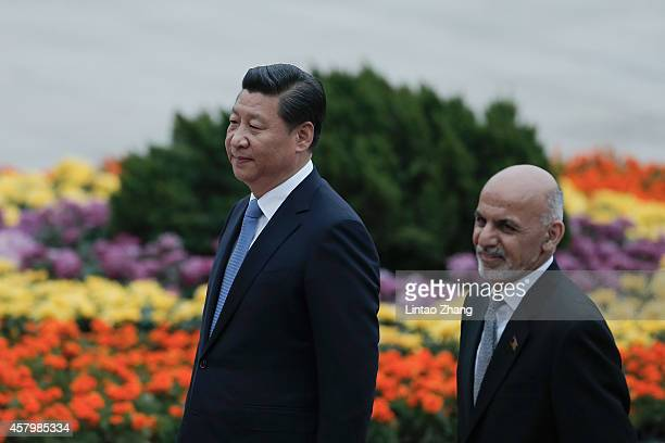 Chinese President Xi Jinping accompanies Afghan President Ashraf Ghani Ahmadzai to view an honour guard during a welcoming ceremony outside the Great...