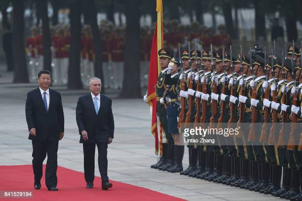 Chinese President Xi Jinping accompanies Brazilian President Michel Temer to view a guard of honour during a welcoming ceremony outside the Great...