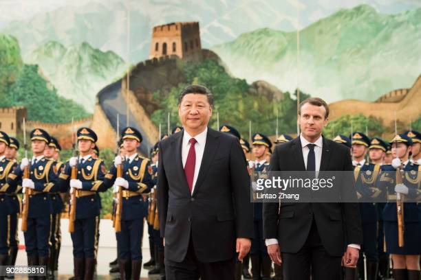 Chinese President Xi Jinping accompanies French President Emmanuel Macron to view an honour guard during a welcoming ceremony inside the Great Hall...