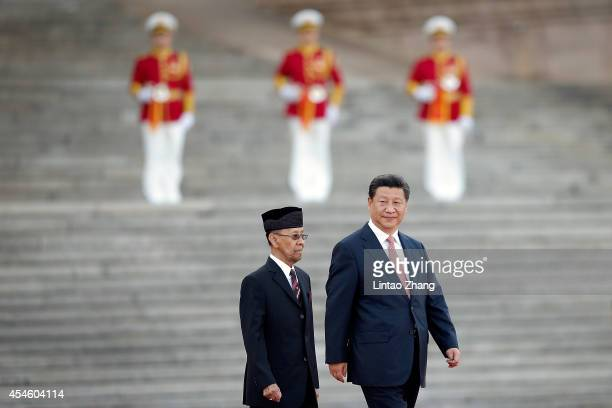 Chinese President Xi Jinping accompanies Malaysia's Yang diPertuan Agong Tuanku Alhaj Abdul Halim Mu'adzam Shah to view an honour guard during a...