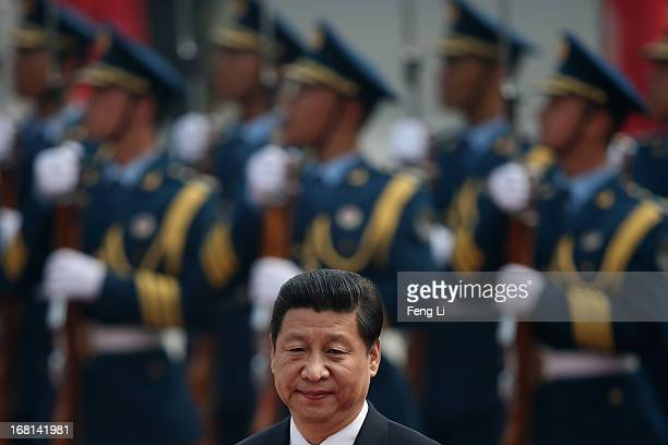 Chinese President Xi Jinping accompanies Palestinian President Mahmoud Abbas to view an honour guard during a welcoming ceremony outside the Great...