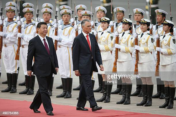 Chinese President Xi Jinping accompanies Portuguese President Anibal Cavaco Silva to view an honour guard during a welcoming ceremony outside the...