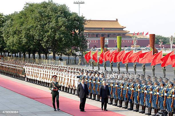 Chinese President Xi Jinping accompanies President Tony Tan Keng Yam of the Republic of Singapore to view an honour guard during a welcoming ceremony...