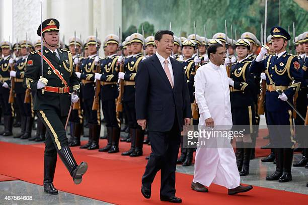 Chinese President Xi Jinping accompanies Sri Lankan President Maithripala Sirisena to view an honour guard during a welcoming ceremony inside the...