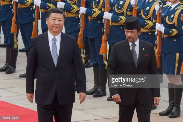 Chinese President Xi Jinping accompanies Sultan of Brunei Hassanal Bolkiah to view a guard of honour during a welcoming ceremony outside the Great...