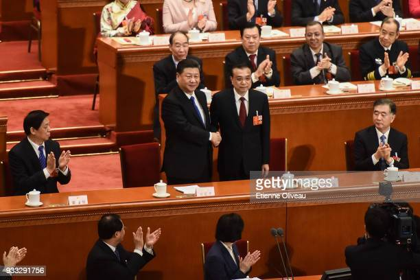 Chinese President Xi Jinping and Chinese Premier Li Keqiang shake hands as delegates applaud following the announcement of parliament approving Li's...