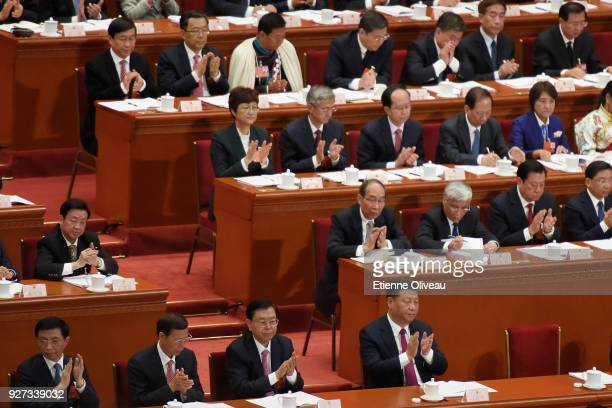 Chinese President Xi Jinping and delegates applaud during the opening session of the 13th National People's Congress at The Great Hall of People on...