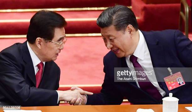 Chinese President Xi Jinping and former president Hu Jintao shake hands during the opening session of the 19th Communist Party Congress held at the...