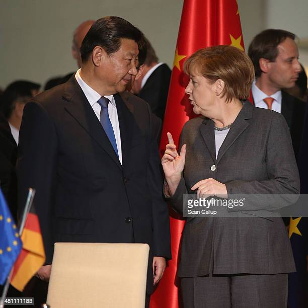 Chinese President Xi Jinping and German Chancellor Angela Merkel chat with the help of an interpreter during the signing of bilateral agreements at...