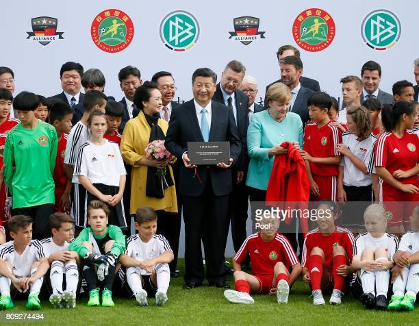 Chinese President Xi Jinping and his wife Peng Liyuan and German Chancellor Angela Merkel get gifts by U12 children of Germany and China during their...